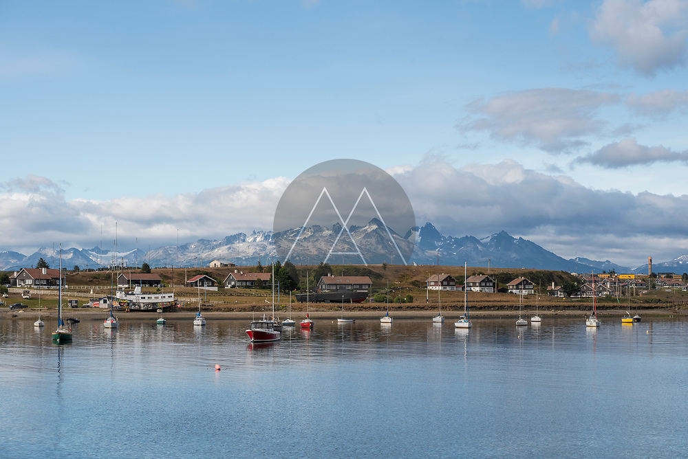 View of a few boats anchored along the waterfront in the bay in Ushuaia, Tierra del Fuego, Patagonia, Argentina.