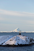 Scenic winter landscape with mountain range covered in snow and Arctic Circle marker, Arnes, Nordland, Norway