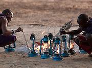 Maasai tribesman lighting Hurrican Lamps at an Eco Tourism Campsite. Near Amboseli National Park, Rift Valley Province, Kenya