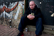 "Homeless man John sitting beside the old Spitalfields underground station entrance in East London. Drinking a can of lager he said ""I'm homeless"", ""I'm alcoholic"". He requested that the photographer send his picture to his mother in Ireland, writing a note to her which read ""To beautiful. My Nora"" and her address. Homelessness is a big problem in all major cities not least in London where there are a great number of people living on the streets and often living as street drinkers."