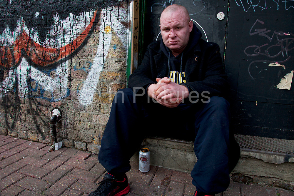 """Homeless man John sitting beside the old Spitalfields underground station entrance in East London. Drinking a can of lager he said """"I'm homeless"""", """"I'm alcoholic"""". He requested that the photographer send his picture to his mother in Ireland, writing a note to her which read """"To beautiful. My Nora"""" and her address. Homelessness is a big problem in all major cities not least in London where there are a great number of people living on the streets and often living as street drinkers."""