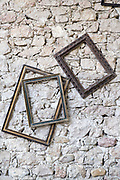 empty picture frames against a rustic stone wall