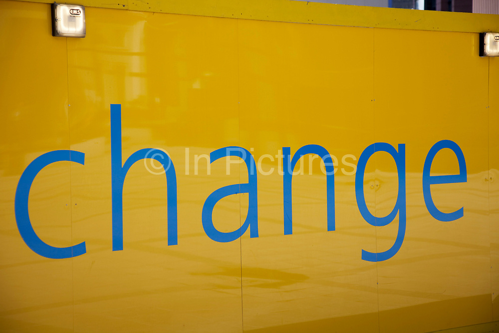 """Yellow oarding sign with the word """"Change"""" written in blue letters."""