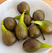 White fruit bowl of figs from above oblique angle close up