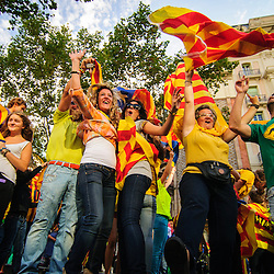 Catalans with Catalan flags pose for photos on an air vent during the National Day of Catalonia.