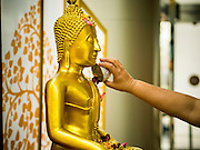 """10 APRIL 2014 - BANGKOK, THAILAND:  A Thai Buddhist bathes a Buddha statue at Siam Paragon, an upscale mall in Bangkok, for Songkran. Many malls put out shrines for Songkran so people can pray and make merit while they shop. Songkran, also called the """"Water Festival"""" is the traditional Thai New Year. It was celebrated as the New Year until 1940, when Thailand made January 1 the official start of the New Year. Songkran is now a three day holiday starting on April 13. Many people go to temples to make merit in the days leading up to Songkran. They bathe Buddha statues to bring themselves good luck in the coming year. The holiday is best known for water fights and throwing water at strangers. Thais and foreigners go out with giant squirt guns or buckets of water and throw the water at strangers.   PHOTO BY JACK KURTZ"""