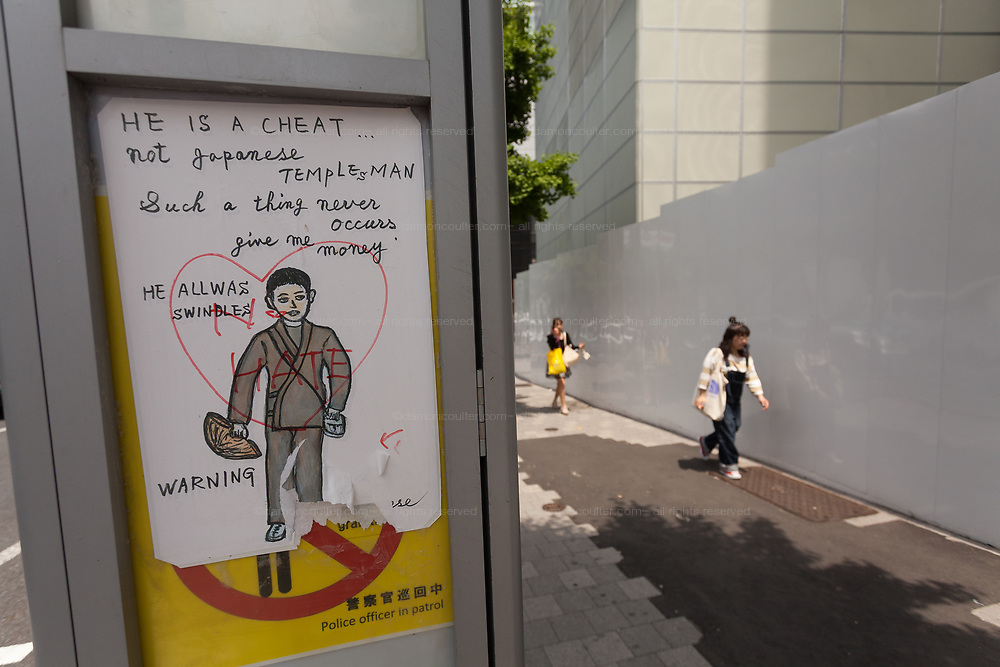A warning sign about false monks who collect money on the street, on a board in Harajuku, Tokyo, Japan. Friday May 12th 2017