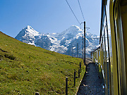 """The mountain peaks of Eiger and Mönch (Ogre and Monk) rise above Wengernalpbahn cog train in Lauterbrunnen Valley, Berner Oberland, Switzerland, the Alps, Europe. Wengernalpbahn, the world's longest continuous rack and pinion railway, goes from Grindelwald up to Kleine Scheidegg and down to Wengen and Lauterbrunnen. From Kleine Scheidegg, another cog train (Jungfraubahn) ascends steeply inside the Eiger to Jungfraujoch, the highest railway station in Europe. A gondola (gondelbahn) connects Grindelwald with Männlichen, where a cable car goes down to Wengen (Luftseilbahn Wengen-Männlichen). The Bernese Highlands are the upper part of Bern Canton. UNESCO lists """"Swiss Alps Jungfrau-Aletsch"""" as a World Heritage Area (2001, 2007)."""