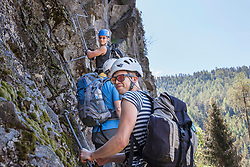 Climbing group scaling rock face via ferrata towards Stuibenfall Waterfall, Otztal, Tyrol, Austria