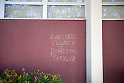 Protestors write on the walls of the Engineering Building with chalk as U.S. Homeland Security Secretary Janet Napolitano discusses cyber security with San Jose State students and faculty on April 16, 2012, at the Engineering Building, San Jose State University, San Jose, Calif.  Photo by Stan Olszewski/SOSKIphoto