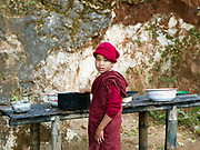 A young Buddhist monk wearing red robes washes dishes after breakfast at Htee Tein village monastery, Shan State, Myanmar (Burma).