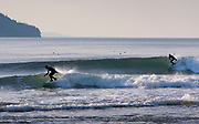 Surfers enjoy a nice 3-5 foot west swell with offshore winds, at the Elwha River mouth west of Port Angeles, WA.