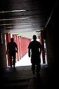 A prisoner and prison officer walking between buildings. HMP The Mount, Bovingdon, Hertfordshire