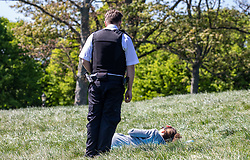© Licensed to London News Pictures. 19/04/2020. London, UK. A policeman speaks to a women laying on the grass as Police patrol Primrose Hill enforcing lockdown rules on social distancing and exercise as Ministers urge councils to keep parks open to the public during lockdown. Photo credit: Alex Lentati/LNP