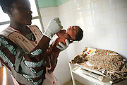 Midwife Dagnoko Alima Dambele weights a newborn child at the Badegna community health center in the town of Kita, Mali on Sunday August 29, 2010.