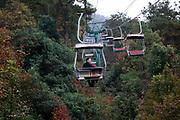 A man and his song rides a lift up the Zijing Mountain in Nanjing, Jiangsu Province, China on 09 November, 2011.