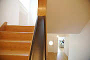 The staircase looking upstairs and downstairs towards the living room, and Wayne's partner, Antoine Vereecken pictured sitting on the sofa at Warren House, Wayne McGregor's Dartington Estate home in Devon<br /> Vanessa Berberian for The Wall Street Journal