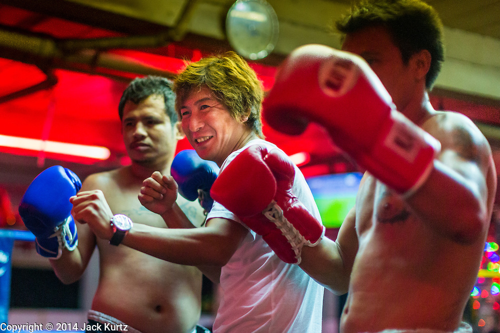 """26 SEPTEMBER 2014 - PATTAYA, CHONBURI, THAILAND: A Korean tourist poses with Muay Thai boxers in a beer bar in Pataya. Pataya, a beach resort about two hours from Bangkok, has wrestled with a reputation of having a high crime rate and being a haven for sex tourism. After the coup in May, the military government cracked down on other Thai beach resorts, notably Phuket and Hua Hin, putting military officers in charge of law enforcement and cleaning up unlicensed businesses that encroached on beaches. Pattaya city officials have launched their own crackdown and clean up in order to prevent a military crackdown. City officials have vowed to remake Pattaya as a """"family friendly"""" destination. City police and tourist police now patrol """"Walking Street,"""" Pattaya's notorious red light district, and officials are cracking down on unlicensed businesses on the beach.     PHOTO BY JACK KURTZ"""