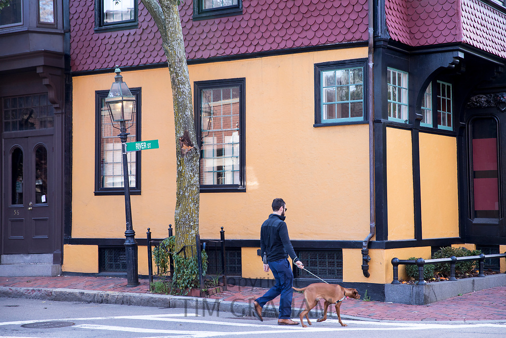 Man walking dog in River Street in the historic district of Boston, Massachusetts, USA
