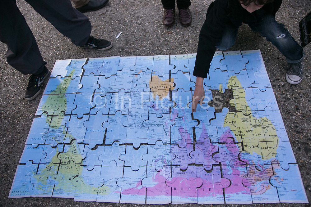 An upside down map of the world puzzle. Citizen Climate Summit in Montreuil. A host of organisations, small NGOs, political art events and food stalls set the scene for discussions and debates on climate change as an alternative to the offical COP21 in Bourget.  The official climate talks in Paris is on and the pressure to come up with a sustainable legally binding is high. In the aftermath of recent terrorist attacks public demonstrations have been banned during the 2 weeks of climate talks