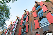 Red shutters and traditional Dutch architecture of canalside buildings in Prinsengracht, Amsterdam, Holland