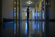 A prisoner walking down the enhanced wing corridor. HMP/YOI Portland, Dorset. A resettlement prison with a capacity for 530 prisoners. Dorset, United Kingdom.