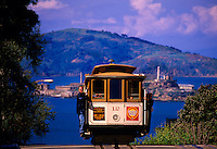 A cable car tops Hyde Street (with Alcatraz island in background), San Francisco, California