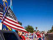 "11 NOVEMBER 2013 - PHOENIX, AZ: An American flag flying on a pickup truck in the Phoenix Veterans Day Parade. The Phoenix Veterans Day Parade is one of the largest in the United States. Thousands of people line the 3.5 mile parade route and more than 85 units participate in the parade. The theme of this year's parade is ""saluting America's veterans.""    PHOTO BY JACK KURTZ"
