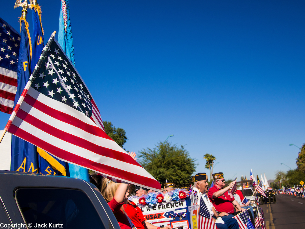 """11 NOVEMBER 2013 - PHOENIX, AZ: An American flag flying on a pickup truck in the Phoenix Veterans Day Parade. The Phoenix Veterans Day Parade is one of the largest in the United States. Thousands of people line the 3.5 mile parade route and more than 85 units participate in the parade. The theme of this year's parade is """"saluting America's veterans.""""    PHOTO BY JACK KURTZ"""