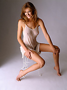 Happy woman in sheer lingerie sitting on bath stool on gray background