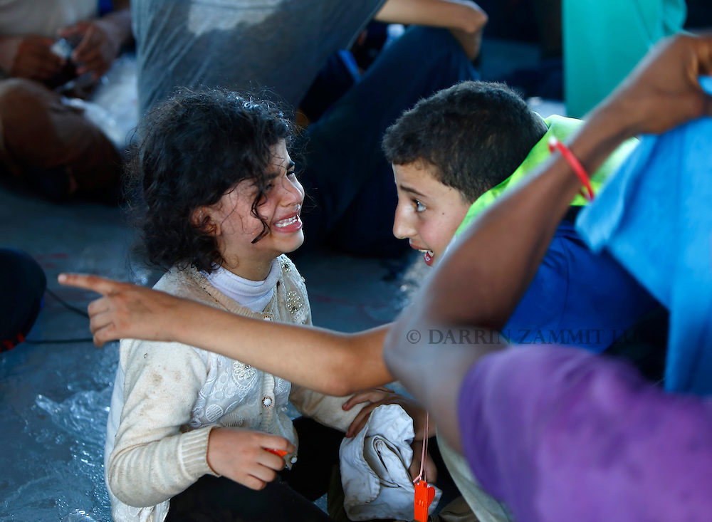 Migrant children cry on the Migrant Offshore Aid Station (MOAS) ship MV Phoenix after being rescued from an overloaded wooden boat 10.5 miles off the coast of Libya August 6, 2015.  An estimated 600 migrants on the boat were rescued by the international non-governmental organisations Medecins san Frontiere (MSF) and MOAS without loss of life on Thursday afternoon, a day after more than 200 migrants are feared to have drowned in the latest Mediterranean boat tragedy after rescuers saved over 370 people from a capsized boat thought to be carrying 600.<br /> REUTERS/Darrin Zammit Lupi <br /> MALTA OUT. NO COMMERCIAL OR EDITORIAL SALES IN MALTA