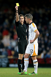 Referee John Brooks shows a yellow card to Port Vale's Michael Tonge