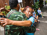 15 AUGUST 2016 - BANGKOK, THAILAND:  A resident of the Pom Mahakan slum hugs a Thai soldier moments after she was told she has being evicted from her home in the slum. Final eviction notices were posted today and residents of the slum have been told they must leave the fort by September 3, 2016. The Pom Mahakan community is known for fireworks, fighting cocks and bird cages. Mahakan Fort was built in 1783 during the reign of Siamese King Rama I. It was one of 14 fortresses designed to protect Bangkok from foreign invaders. Only two of the forts are still standing, the others have been torn down. A community developed in the fort when people started building houses and moving into it during the reign of King Rama V (1868-1910). The land was expropriated by Bangkok city government in 1992, but the people living in the fort refused to move. In 2004 courts ruled against the residents and said the city could take the land.     PHOTO BY JACK KURTZ