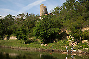 Kids playing along the river in the medieval village of Lagrasse, Languedoc-Roussillon, France. Lagrasse is known as one of the most beautiful French villages. It lies in the valley of the River Orbieu and is famous for its stone bridge and The Abbey of St. Mary of Lagrasse, Abbaye Sainte-Marie de Lagrasse, a Romanesque Benedictine abbey.