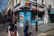 Street scene in Whitechapel in East London, England, United Kingdom. Two Muslim women walk past a digital camera shop advertisment for passport photos.