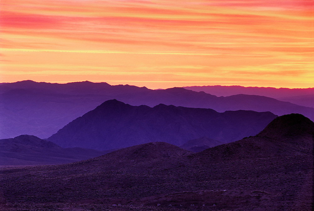 Death Valley, California.<br /> Some years ago, I was coming up out of Death Valley headed towards Soshone, and found a place to stop as the landscape was being lit up by the lowering sun.  After the sun actually set , the color deepened on the thin cloud layers, and cast the mountains westward in hues of blue and purple that seemed to glow as the heat rose, to hang in a haze between the ranges.  This was one of those sunsets that lingered on and on. <br />  Nikon F5, Nikkor 28-70 f/2.8, Velvia (40), 1.5 seconds @ f/16.