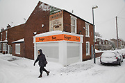 Man walks past a tanning salon in Kings Heath head out to enjoy the heavy snow fall on Sunday 10th December 2017 in Birmingham, United Kingdom. Deep snow arrived in much of the UK, closing roads and making driving treacherous, while many people simply enjoyed the weather.