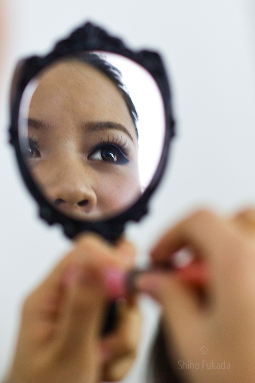 """A participant of """"Miss. International"""" beauty contest puts on makeup before the show in Beijing, China, Nov. 7, 2009."""