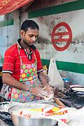 A cook who has put up a temporary tent next to the Metro construction, Vasant Vihar, New Delhi, India