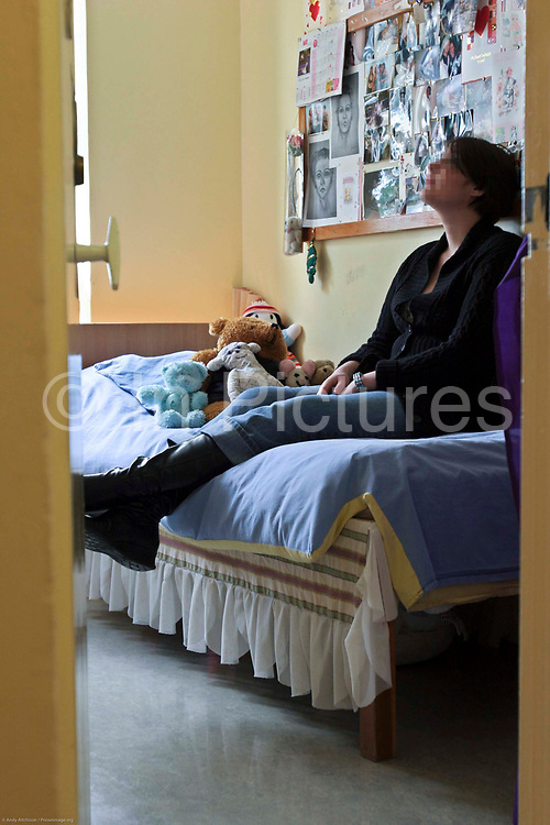 A female prisoner sitting on the bed in her cell at HMP Downview.