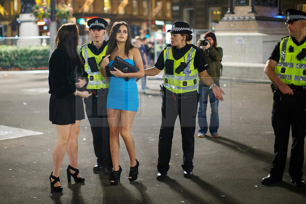 © Licensed to London News Pictures. 19/09/2014. Glasgow, UK. A group of young women on a night out caught in a police line whilst pro-unionists and Scottish independence supporters being separated at George Square in Glasgow as Scotland decides to stay in the union and First Minister Alex Salmond resigns over the results of the Scottish independence referendum on Friday, 19 September 2014. Photo credit : Tolga Akmen/LNP