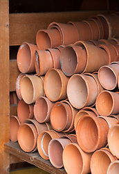 Piles of terracotta pots stored in a shed at West Dean Kitchen Gardens, West Sussex
