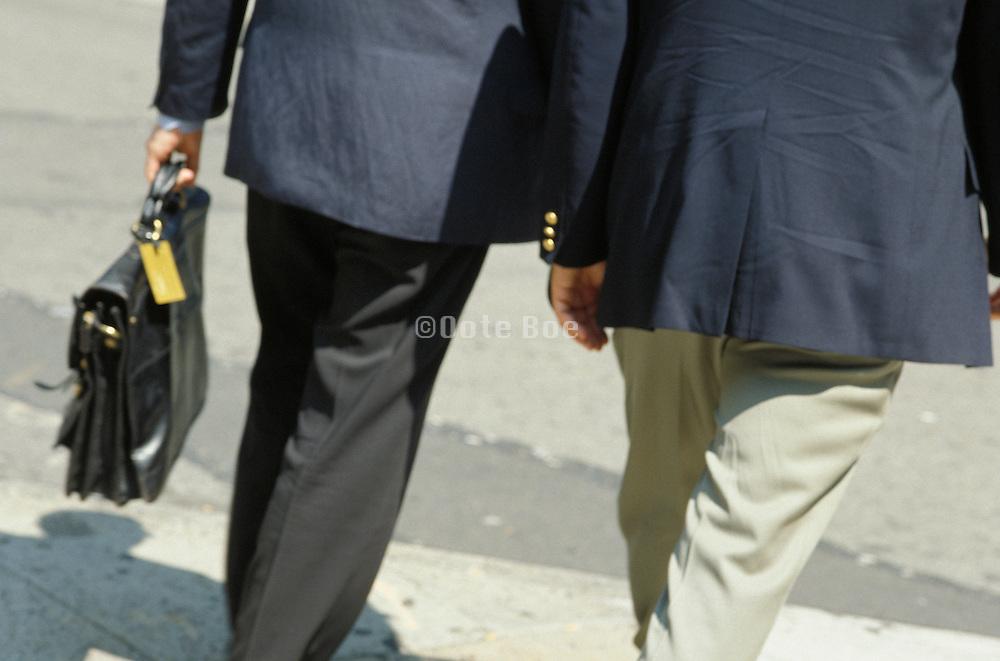 2 businessmen walking in urban environment