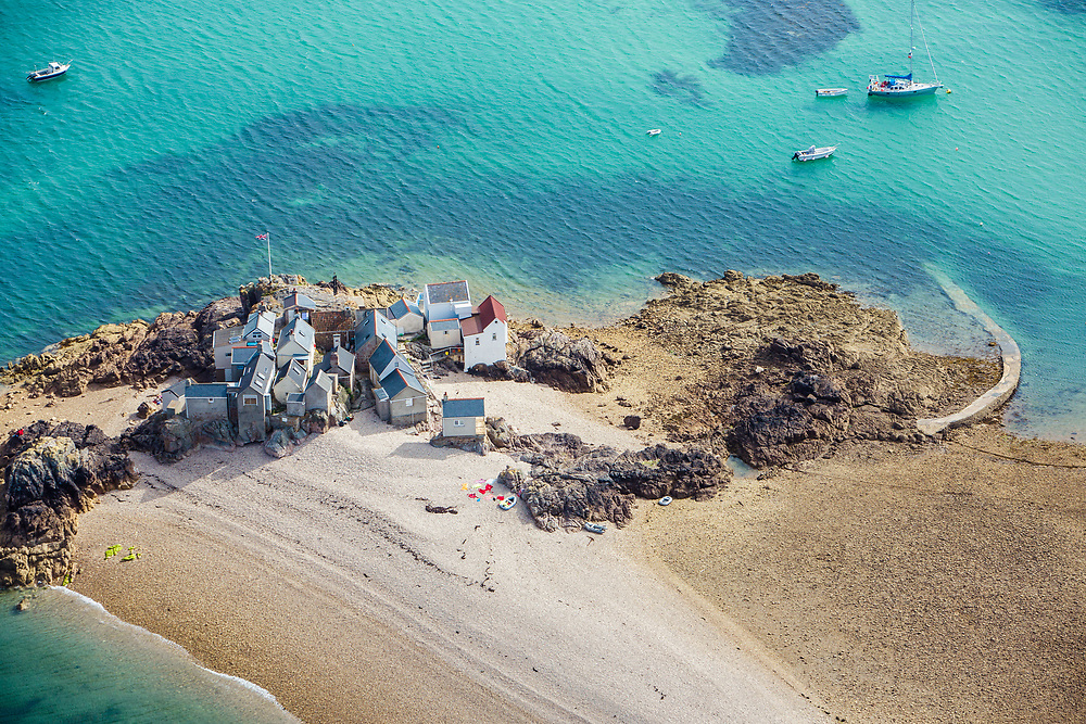 Aerial view of the houses on the Ecrehous, surrounded by turquoise, clear water in Jersey, Channel Islands