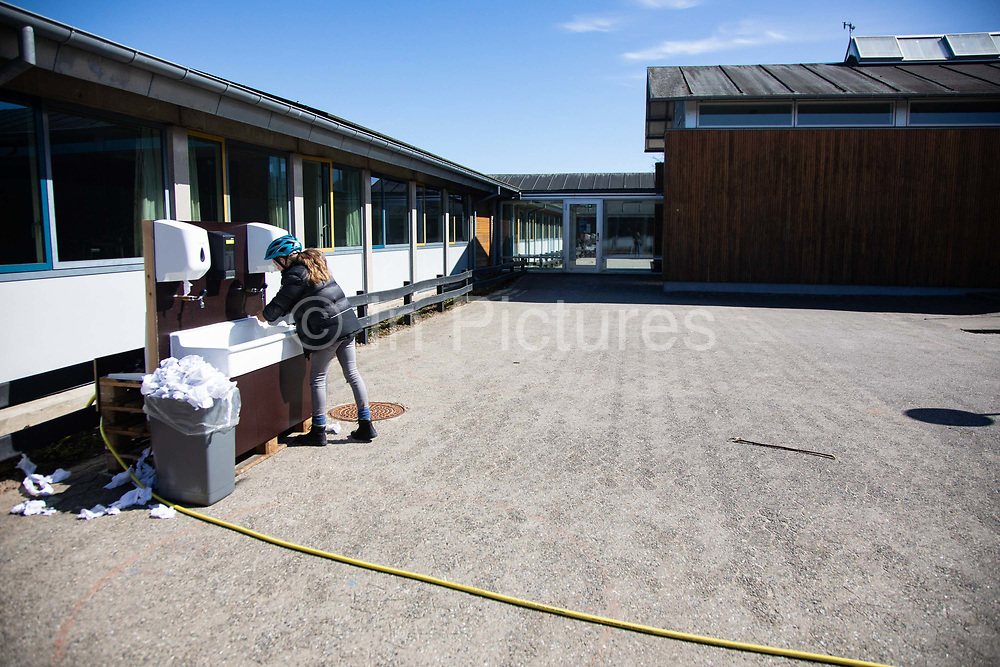 A school girl washes her hands in a temporary sink in the school yard, back in school after 4 weeks of coronavirus lock-down on April 17th 2020 in Aarhus  Denmark. All schools and much of Denmark including its borders were shut Monday March 16th by the Danish Prime Minister Mette Frederiksen to prevent the corona virus from spreading beyond control. All school children had to stay at home if possible during the lock-down and many had not seen their friends through-out the 4 weeks it lasted. All teaching was done at home and via online services such as Google Meet and to many time was difficult to pass. Only year 0-5 are now allowed back in school and only under special measures. Classes are split in twos and across two rooms, everyone must wash hands rigorously when they leave and enter the class and the children must observe distance when possible. The children are put together in groups of no more than three and they are the only ones they get to work  and play with. Break time has to be in designated areas only and only with class mates.