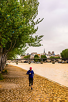 People jogging on the banks of the Seine River (with Pont des Arts behind), Paris, France.
