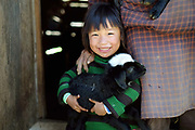 Sheep farmer's grand-daughter holds a small lamb at a sheep farm in Chubja, Bhutan. With the easy availability of commercially processed wool and other alternatives for fabric for weaving, and the lack of human resources to look after the sheep, farming of sheep has gradually been in decline in Bhutan.