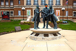 """The statue of Abraham Lincoln, Jesse Fell and David Davis in front of the McLean County Center for the Performing Arts has been """"masked"""" for the COVID-19 (Novel Coronavirus)) by the #blonoyarnbomb"""