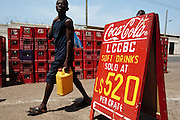 A boy walks past a sign advertising soft drinks for sale at Rally Time market in Monrovia, Montserrado county, Liberia on Thursday April 5, 2012.