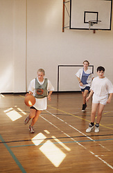 Secondary school pupils playing game of basketball during indoor PE lesson,